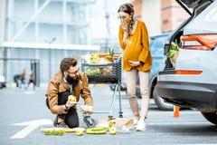 Hombre que ayuda a la mujer embarazada joven cerca del supermercado fotografía de archivo