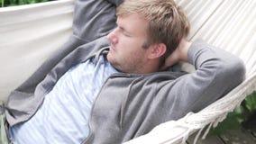 Hombre que balancea en una hamaca en el país almacen de video