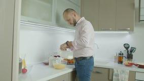 Hombre que bate los huevos y la leche con el mezclador eléctrico almacen de video
