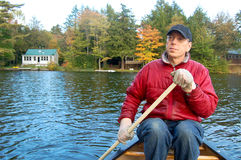 Hombre que bate una canoa en el follaje de otoño de Vermont foto de archivo