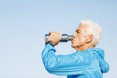 Hombre que bebe de una botella de los deportes Foto de archivo