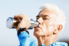 Hombre que bebe de una botella de los deportes Imagenes de archivo