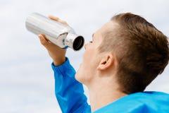 Hombre que bebe de una botella de los deportes Foto de archivo libre de regalías
