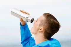 Hombre que bebe de una botella de los deportes Fotos de archivo
