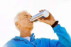 Hombre que bebe de una botella de los deportes Imágenes de archivo libres de regalías