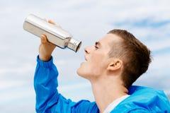 Hombre que bebe de una botella de los deportes Fotografía de archivo