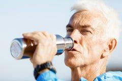 Hombre que bebe de una botella de los deportes Fotos de archivo libres de regalías