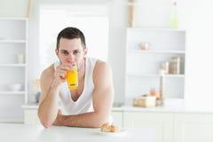 Hombre que bebe el zumo de naranja Foto de archivo