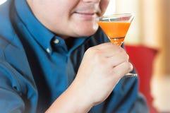 Hombre que bebe el zumo de naranja Imágenes de archivo libres de regalías