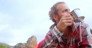Hombre que bebe la bebida caliente 4k almacen de metraje de vídeo