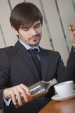 Hombre que bebe por el trabajo de oficina Imagen de archivo