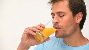 Hombre que bebe un vidrio de zumo de naranja almacen de video