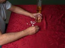 Hombre que bebe y que toma píldoras Foto de archivo libre de regalías