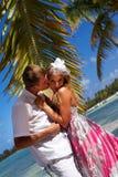Hombre que besa a la mujer en la playa tropical Imagen de archivo