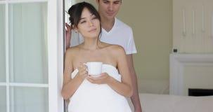 Hombre que besa a la mujer en toalla en la entrada almacen de metraje de vídeo