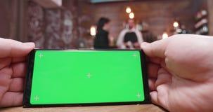 Hombre que birla en un teléfono de pantalla verde en un restaurante, una cafetería o un pub ocupada almacen de metraje de vídeo