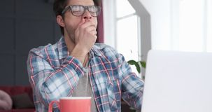 Hombre que bosteza mientras que trabaja en el ordenador portátil metrajes
