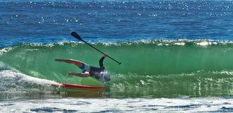 Hombre que cae apagado un paddleboard Fotos de archivo
