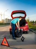Hombre que cambia la rueda pinchada en el coche quebrado Imágenes de archivo libres de regalías