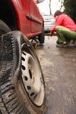 Hombre que cambia un neumático en la calle Fotografía de archivo libre de regalías