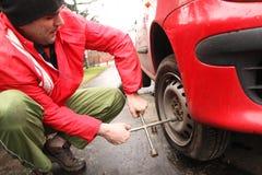 Hombre que cambia un neumático en la calle Fotos de archivo libres de regalías