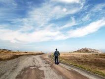 Hombre que camina abajo de la grava y del camino de tierra Imagen de archivo