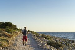 Hombre que camina al aire libre en el océano del cierre del camino que mira el sol que va abajo Foto de archivo libre de regalías