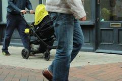 Hombre que camina con el caminante del bebé imagen de archivo