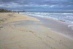 Hombre que camina con fútbol en la playa Imagen de archivo