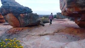 Hombre que camina con las formaciones de roca 4k almacen de video