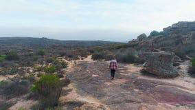 Hombre que camina con las formaciones de roca 4k metrajes