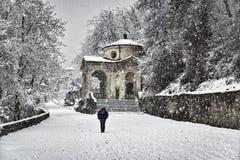 Hombre que camina debajo de la nieve imagenes de archivo