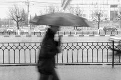 Hombre que camina debajo de un paraguas en la lluvia imagen de archivo
