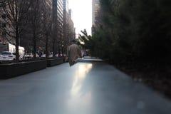 Hombre que camina en el abrigo de invierno que lleva de la acera fotos de archivo