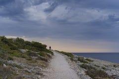 Hombre que camina en el camino en el cierre de la tarde el mar adriático en Croacia Fotos de archivo libres de regalías