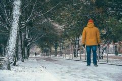 Hombre que camina en el camino de la nieve Imágenes de archivo libres de regalías