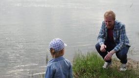 Hombre que camina en el lago con su hijo El papá camina con su hijo por el río un hombre se pone en cuclillas delante de su hijo almacen de metraje de vídeo