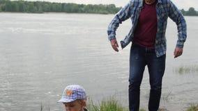 Hombre que camina en el lago con su hijo El pap? camina con su hijo por el r?o un hombre se pone en cuclillas delante de su hijo almacen de video