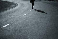 Hombre que camina en el medio del camino Imágenes de archivo libres de regalías