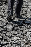 Hombre que camina en la ecología agrietada de la tierra del desierto Fotografía de archivo