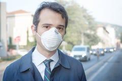 Hombre que camina en la máscara de la protección de la ciudad que lleva contra el aire de la niebla con humo imagenes de archivo