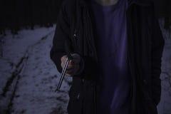 Hombre que camina en la noche con un cuchillo imagenes de archivo