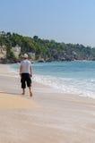 Hombre que camina en la playa Fotografía de archivo libre de regalías
