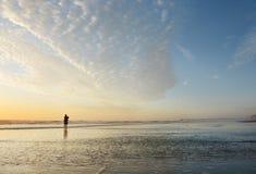 Hombre que camina en la playa en la salida del sol Foto de archivo