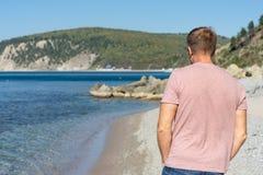 Hombre que camina en la playa Pebble Beach hermoso, cielo azul y mar imagen de archivo