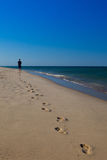 Hombre que camina en la playa que sale de huellas Imágenes de archivo libres de regalías
