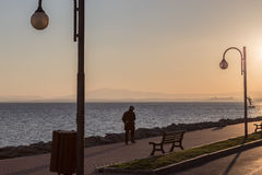 Hombre que camina en la puesta del sol en el lago imagenes de archivo