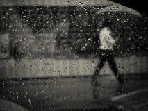 Hombre que camina en lluvia con el paraguas Foto de archivo libre de regalías