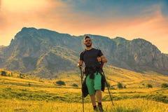 Hombre que camina en montañas verdes Imágenes de archivo libres de regalías