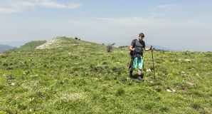 Hombre que camina en montañas verdes Fotos de archivo libres de regalías